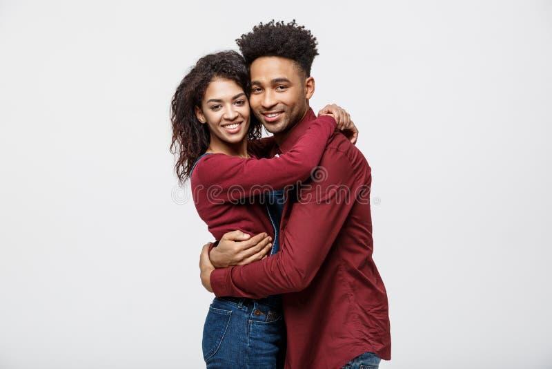 Härliga unga afrikanska par för stående som nästan står och ler på kameran, medan isolerat på vit royaltyfria bilder