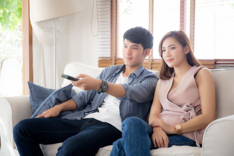 Härliga unga asiatiska par som rymmer fjärrkontrollen och håller ögonen på tv eller videoen som strömmar på soffan med, kopplar a arkivfoto