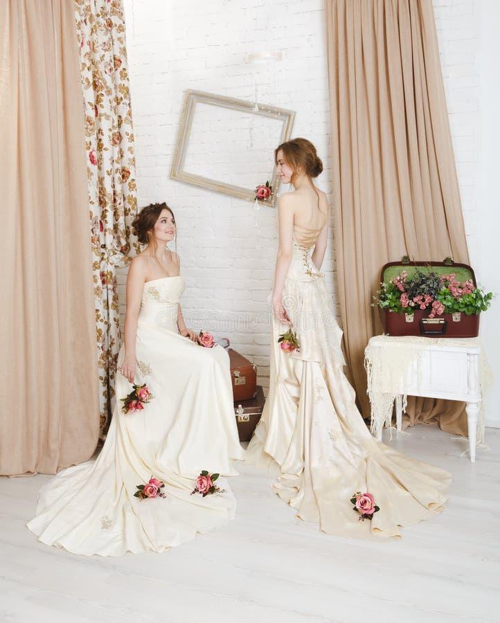 Härliga unga brudar i lantliga bröllopsklänningar arkivfoto