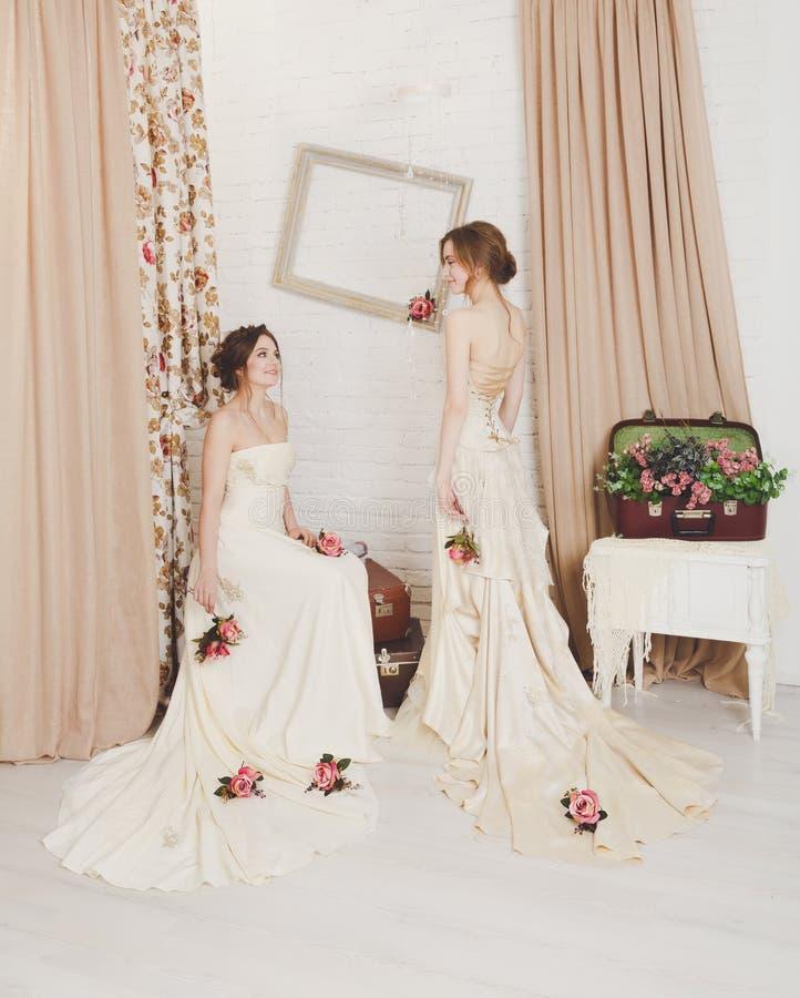 Härliga unga brudar i lantliga bröllopsklänningar royaltyfri foto