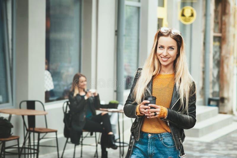 Härliga unga europeiska kvinnakläder i modekläder och att bli framme av den svarta koppen kaffe för kafé och för innehav, royaltyfri fotografi