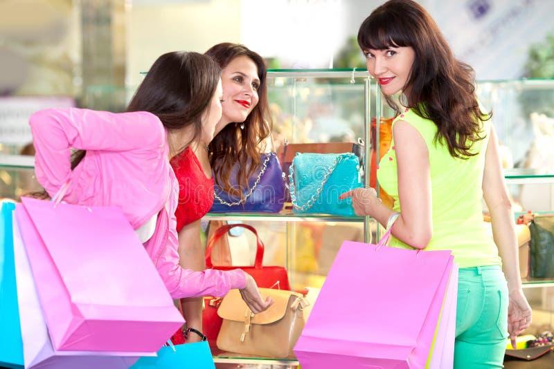 H?rliga unga flickor med shoppingp?sar i gallerian arkivbilder