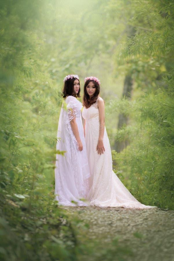 Härliga unga kvinnor i den vita klänningen med blomman på hennes hår ut royaltyfria bilder