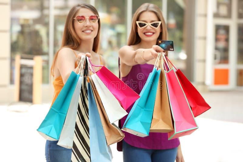 Härliga unga kvinnor med shoppingpåsar och kreditkort på stadsgatan royaltyfri bild