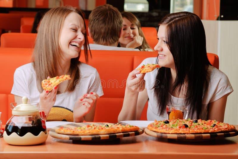 Härliga unga kvinnor som äter pizza royaltyfri bild