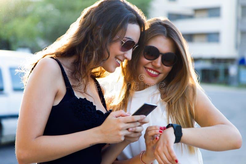 Härliga unga kvinnor som använder en smartwatch i gatan fotografering för bildbyråer