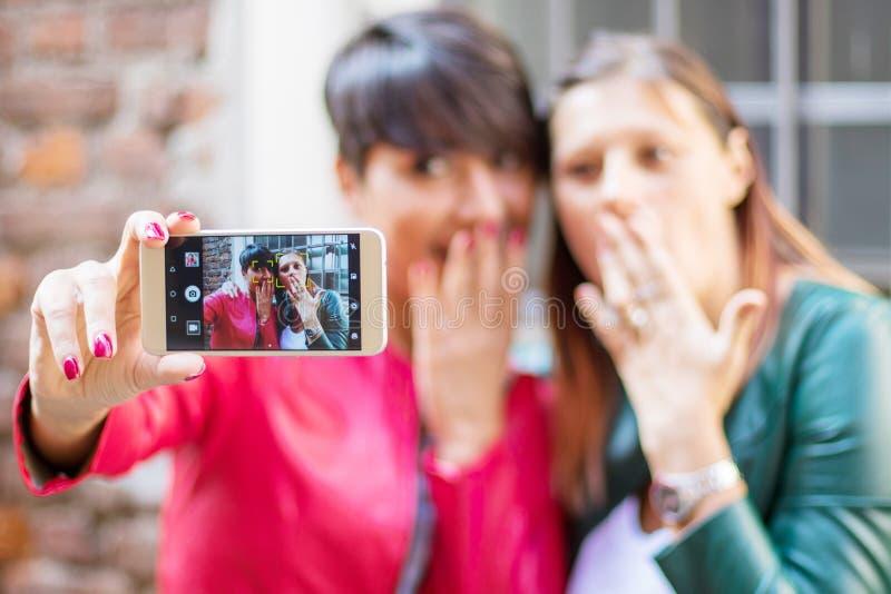 härliga unga kvinnor som gör selfie i staden med en smartphone arkivbild