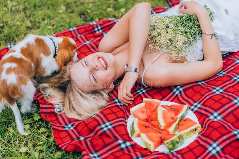Härliga unga kvinnor som lägger på plädet nära vattenmelon som spelar med hunden Natur picknick Copyspace royaltyfri foto