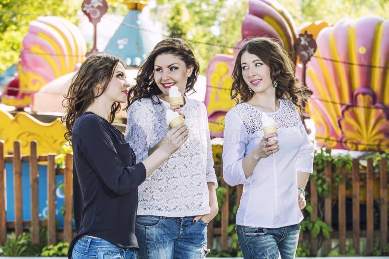 Härliga unga kvinnor som ler äta glass och tala i th arkivbilder