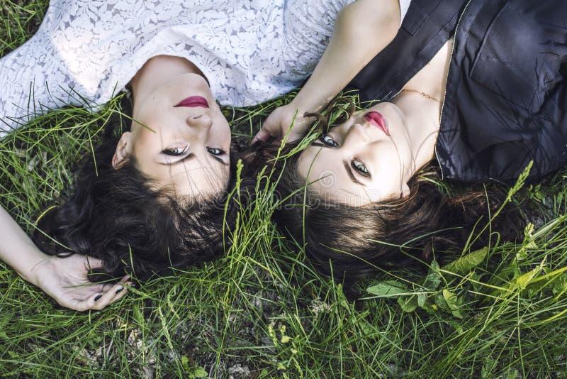 Härliga unga kvinnor som ler lyckligt att ligga i gräset i summ arkivbilder
