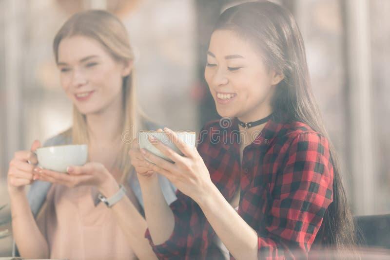 Härliga unga kvinnor som rymmer vita koppar och dricker nytt kaffekaffe royaltyfria bilder