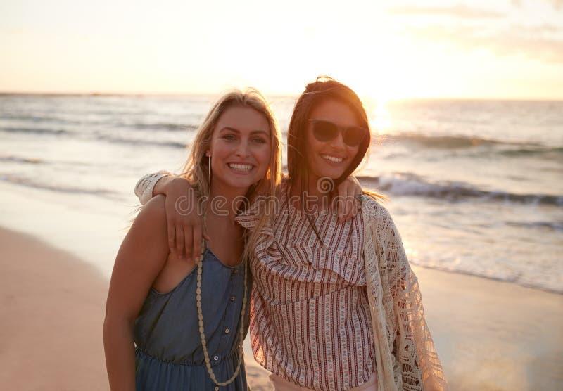 Härliga unga kvinnor som tillsammans står på stranden royaltyfri foto