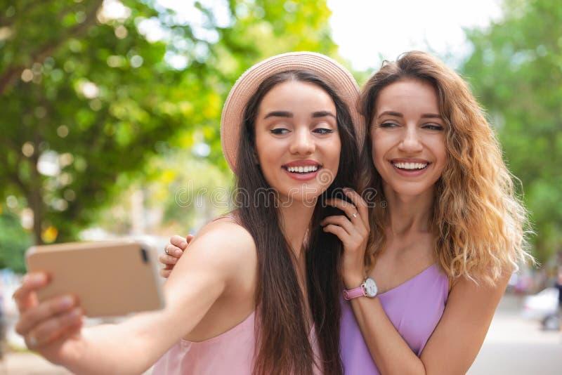 Härliga unga kvinnor som utomhus tar selfie på soligt arkivfoto