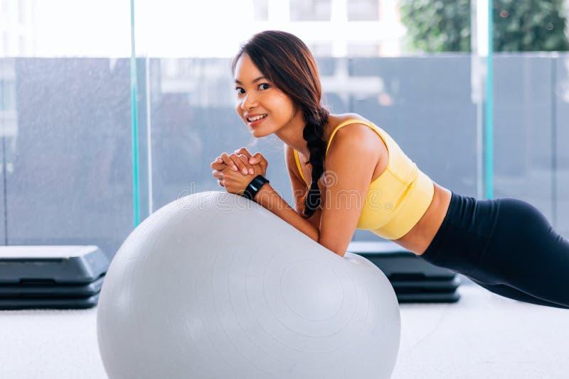 Härliga unga le asiatiska kvinnautbildningspilates, yogaplanka på idrottshallen med övningsbollen arkivfoto