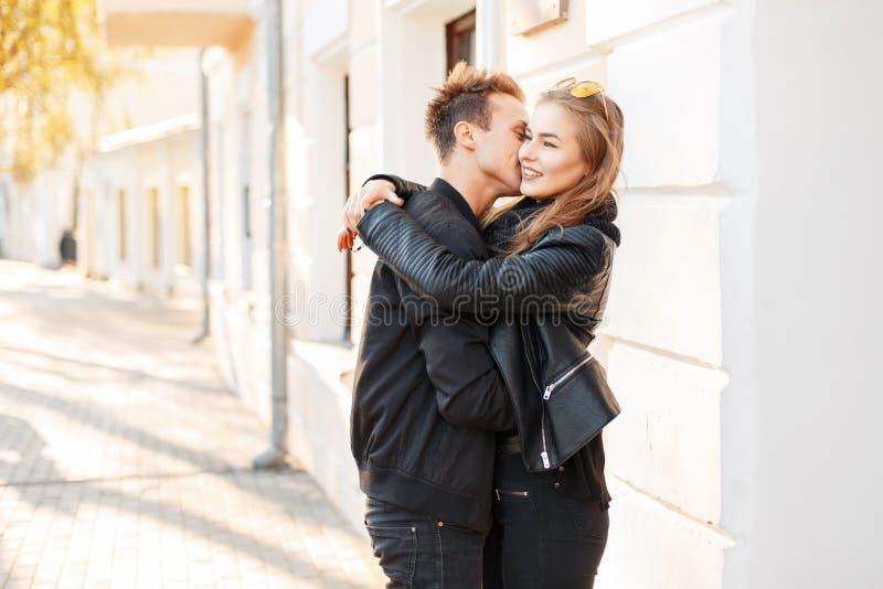 Härliga unga lyckliga par som kysser i staden på en solig dag royaltyfri foto