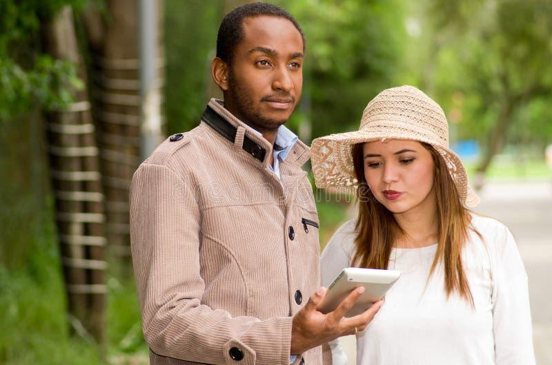 Härliga unga mång--person som tillhör en etnisk minoritet par som har gyckel tillsammans på parkera, man som någonstans ser medan royaltyfri foto