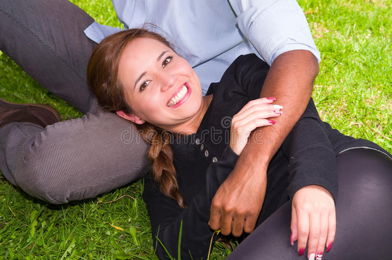 Härliga unga mellan skilda raser par i sammanträde arbeta i trädgården miljön som lyckligt omfamnar och ler till kameran royaltyfria bilder