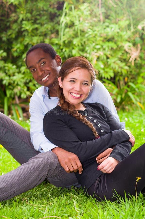 Härliga unga mellan skilda raser par i sammanträde arbeta i trädgården miljön som lyckligt omfamnar och ler till kameran arkivbilder