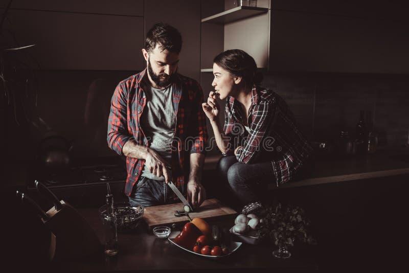 Härliga unga par i kök hemma, medan laga mat sund mat Mannen är snittsallad Kvinnan sitter på tabellen och att äta en gurka royaltyfri fotografi