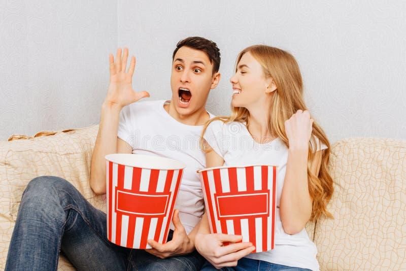 Härliga unga par, man och kvinna, håller ögonen på filmer och att äta popcorn som hemma sitter på soffan fotografering för bildbyråer