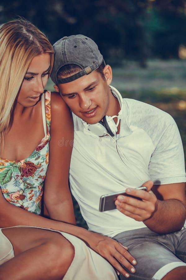 Härliga unga par som använder den smarta telefonen under picknick i, parkerar arkivbild