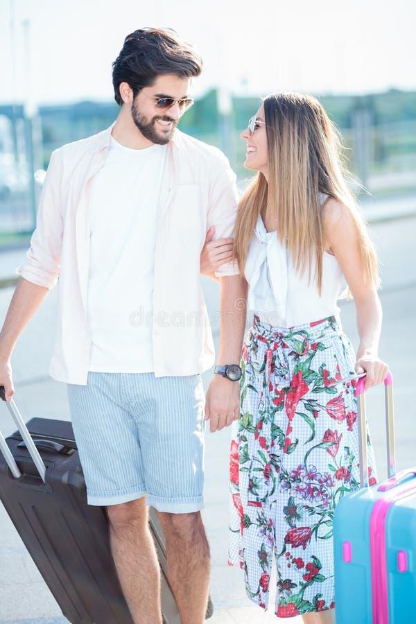 Härliga unga par som går med resväskor som ankommer till en flygplatsterminal arkivbild
