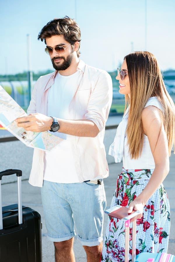 Härliga unga par som går med resväskor som ankommer till en flygplatsterminal arkivfoto