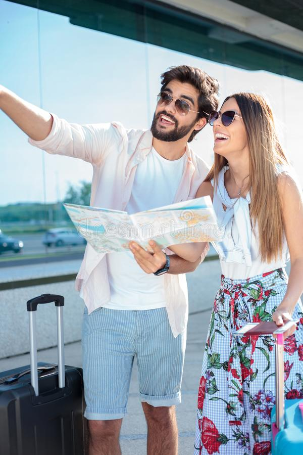 Härliga unga par som går med resväskor som ankommer till en flygplatsterminal arkivbilder