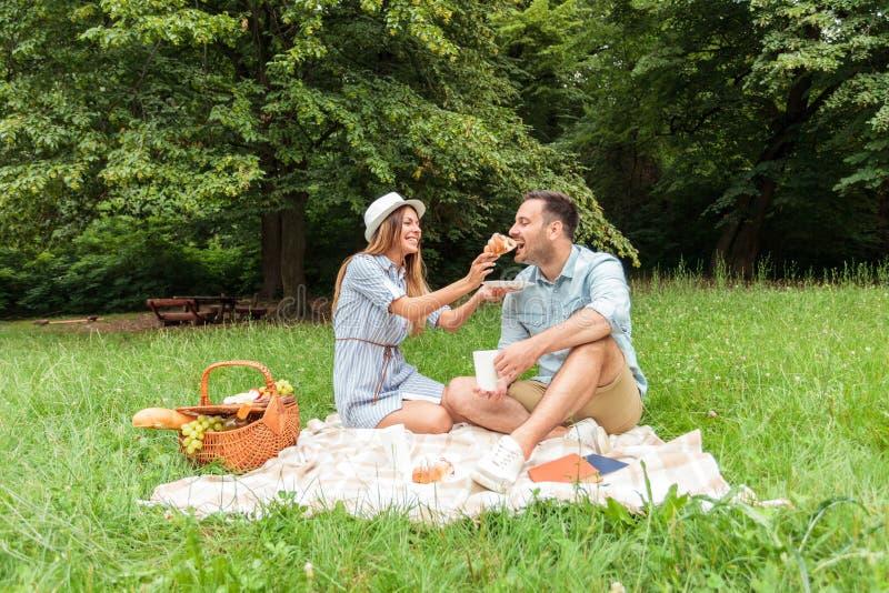 Härliga unga par som har en avslappnande picknick i, parkerar arkivfoton