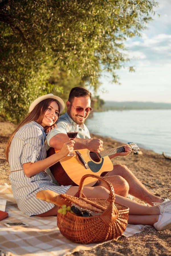 Härliga unga par som kopplar av på stranden och att spela gitarren och att sjunga arkivfoton