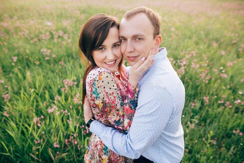 Härliga unga par som kramar och ler försiktigt i solsken i ny våräng med rosa blommor Lycklig stilfull familj arkivbild