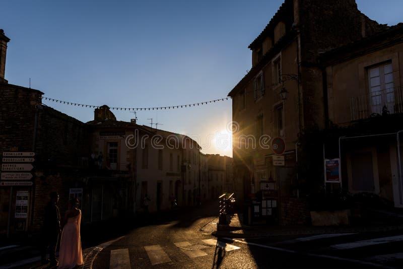 härliga unga par som rymmer händer och går på gatan med gamla hus på solnedgången arkivbild