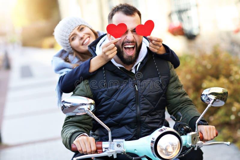 Härliga unga par som rymmer hjärtor, medan rida sparkcykeln i stad i höst arkivfoton