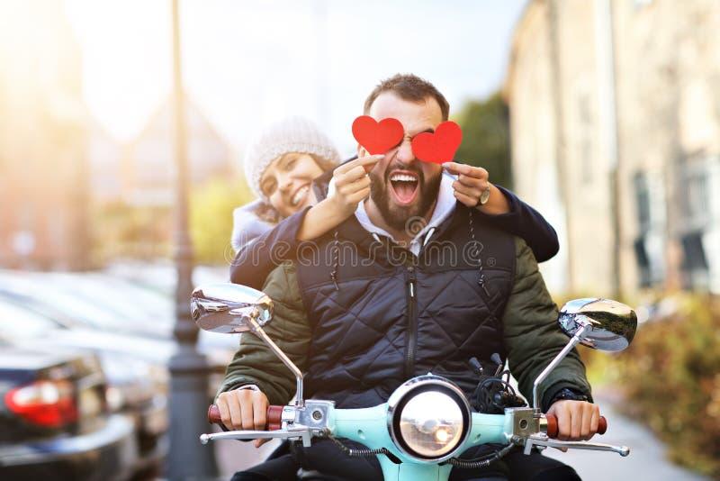 Härliga unga par som rymmer hjärtor, medan rida sparkcykeln i stad i höst arkivfoto
