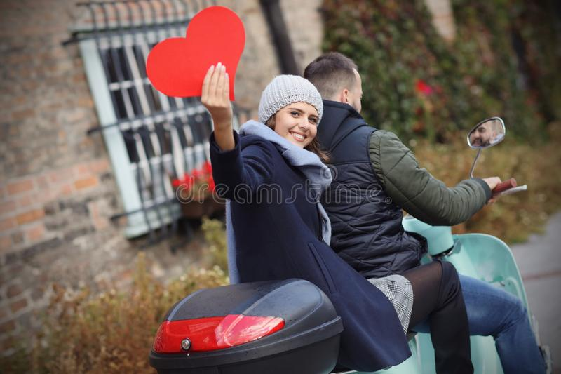 Härliga unga par som rymmer hjärtor, medan rida sparkcykeln i stad i höst fotografering för bildbyråer