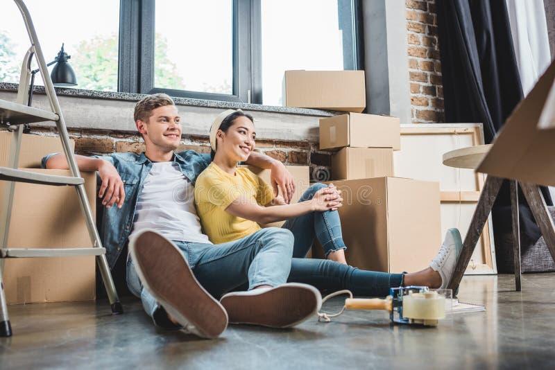 härliga unga par som sitter på golv på det omgivna nya hemmet arkivbilder