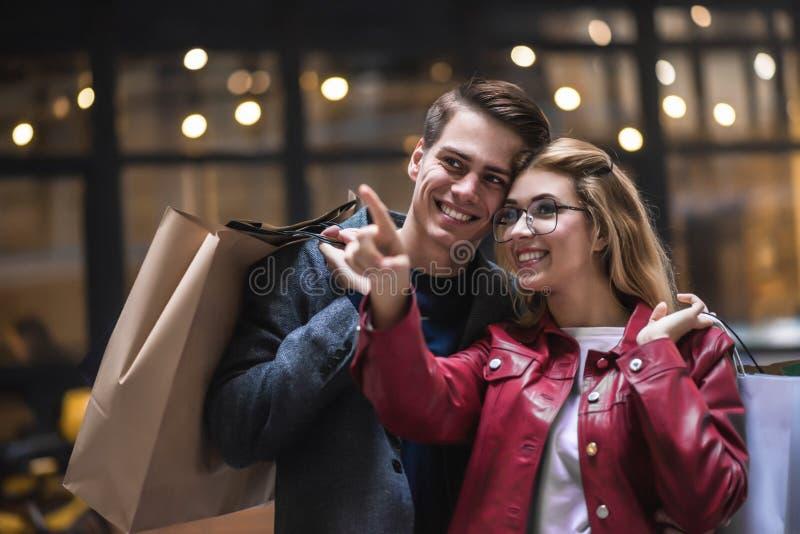 Härliga unga par som tillsammans tycker om i shopping och att ha gyckel Consumerism förälskelse som daterar, livsstilbegrepp royaltyfri foto