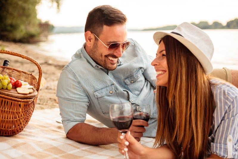 Härliga unga par som tycker om picknicken på en strand fotografering för bildbyråer