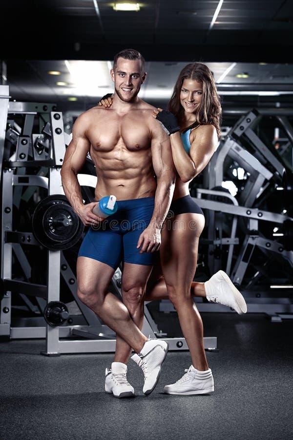 Härliga unga sportiga sexiga par i idrottshall royaltyfri foto