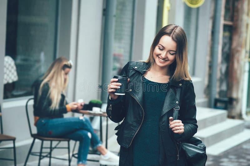 Härliga unga stilfulla tillfälliga kvinnakläder i modekläder och bli på den svarta koppen kaffe för gata och för innehav arkivfoto
