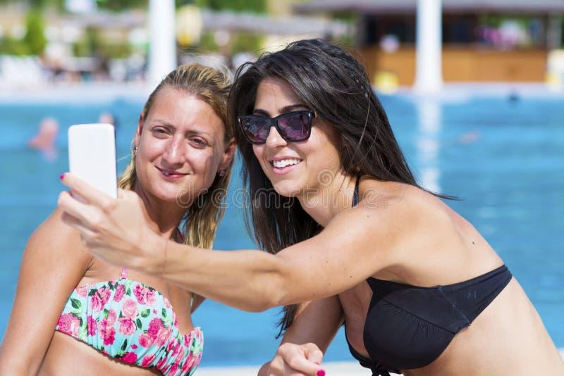 Härliga unga vänner som skrattar och gör selfie på pölen fotografering för bildbyråer
