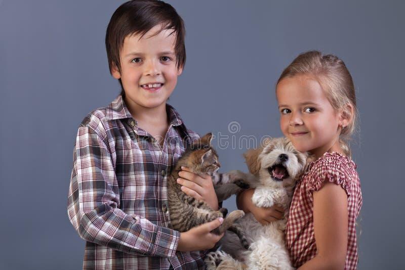 Härliga ungar med deras älskvärda husdjur royaltyfria bilder