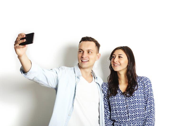 Härliga upphetsade unga raka par som gör roliga framsidor, skrattar, ler & tar selfie och att ha gyckel med den mobila mobiltelef royaltyfri foto