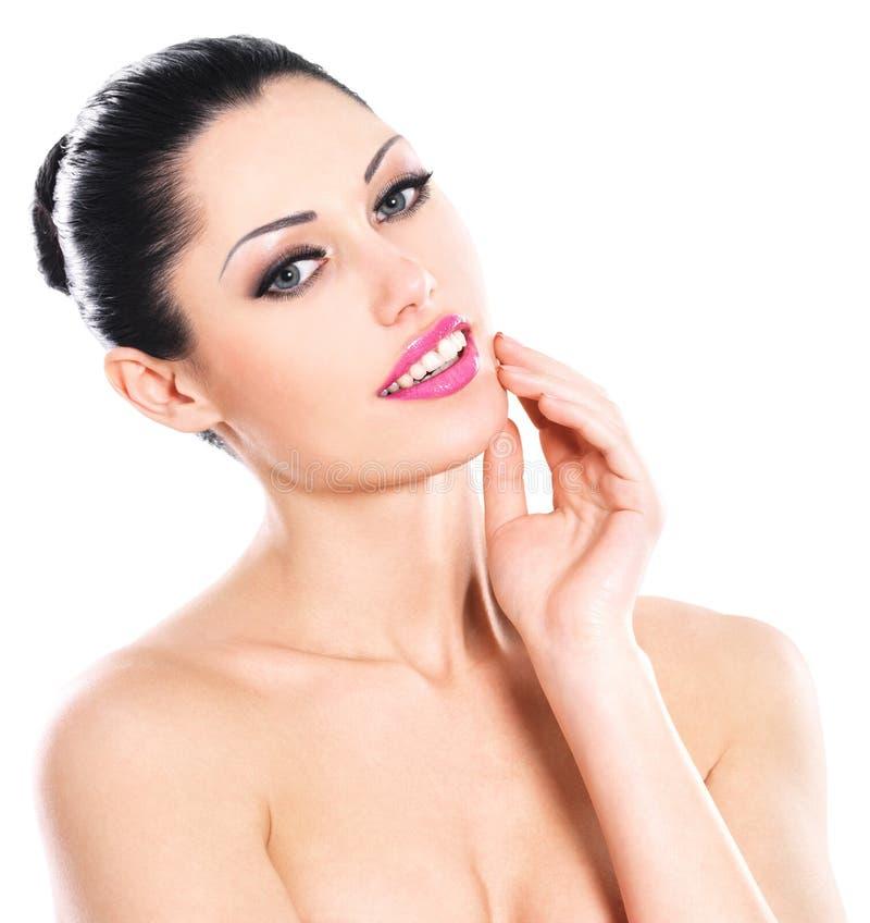 Härliga uttrycksfulla kvinnaomsorger av huden vänder mot arkivfoto