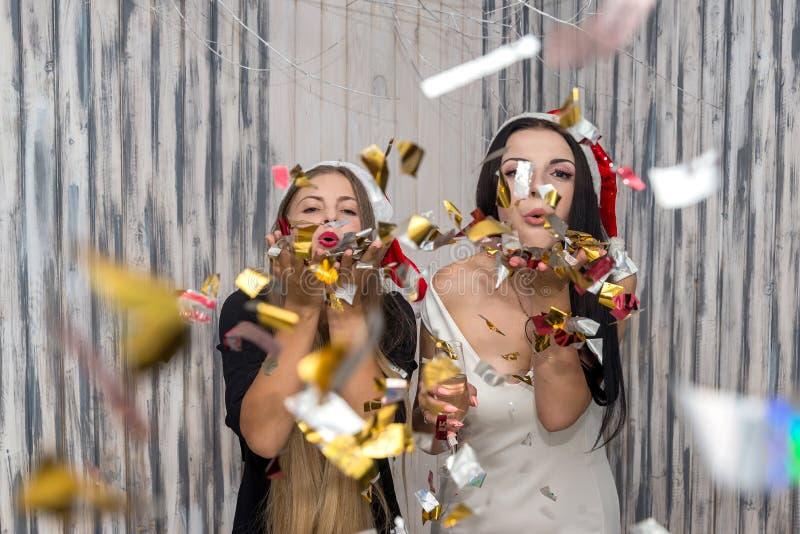 Härliga vänner som blåser ut att moussera konfettier i studio royaltyfria foton