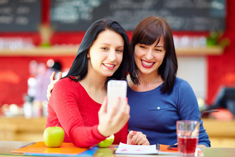 Härliga vänner som tar en självstående med telefonen i kafé fotografering för bildbyråer