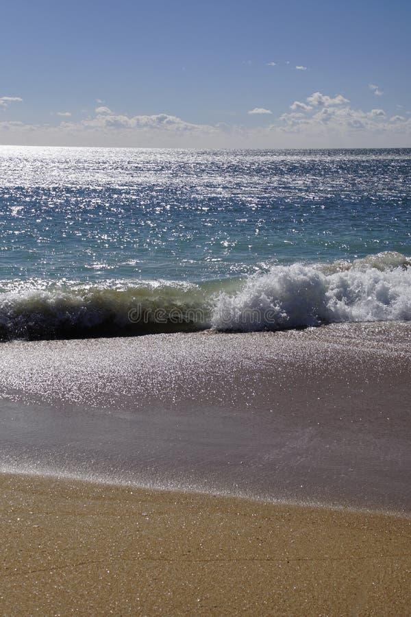 Härliga vågor för havkust av bränningen i strålarna av solen Sandig strand r arkivbild