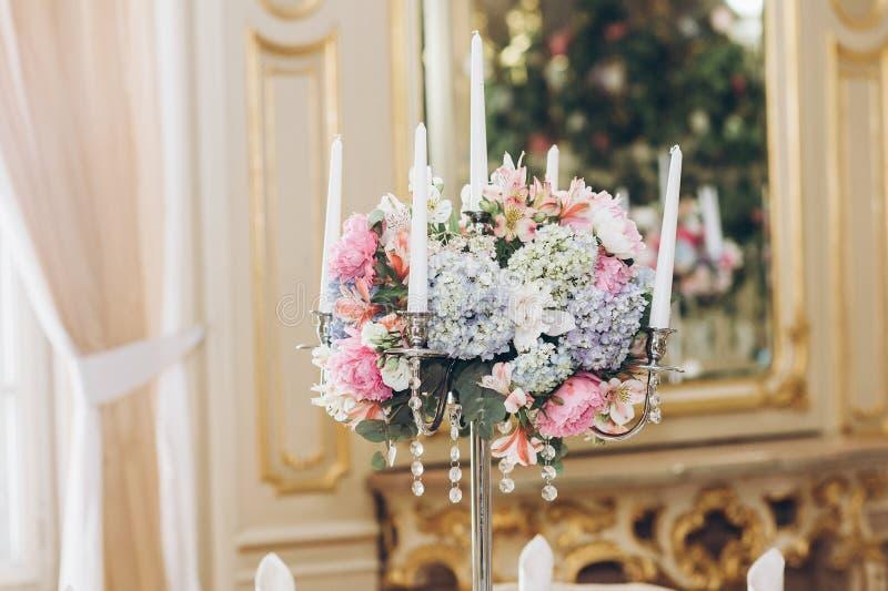 Härliga vanlig hortensiabuketter i vaser och skinande silvercandelabr fotografering för bildbyråer