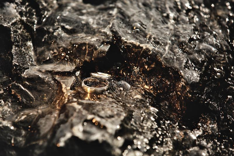 Härliga vigselringar ligger på stenarna, på som vattenflödena Vigselringdetaljer av den gifta sig dagen royaltyfria foton
