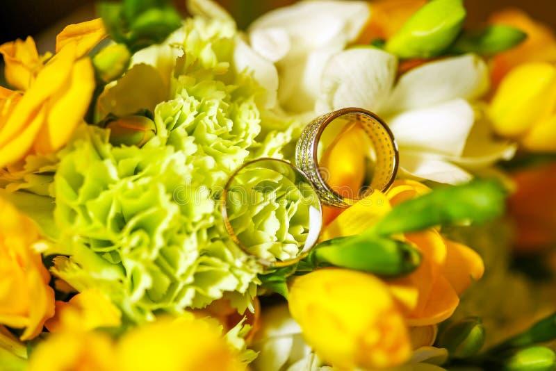 Härliga vigselringar på de ljusa blommorna för vår arkivfoto